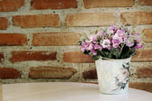 Pink artificial flower on cement brick wall background — Stock Photo