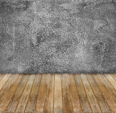Abandoned aged grunge cement wall and yellow wooden floor — Stock Photo