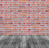 Brown red brick wall and black wooden floor background — Stock Photo