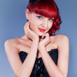 Studio portrait of young woman in little hat and corset in pin-up style — Stock Photo #10241236