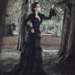 Woman in forest in black dress — Foto de Stock