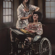 Mad nurse with sick patient in wheelchair — Stock Photo