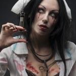 Dead nurse holding syringe with blood — Stock Photo