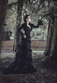 Mujer en bosque en vestido negro — Foto de Stock