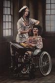 Gekke verpleegster met zieke patiënt in rolstoel — Stockfoto