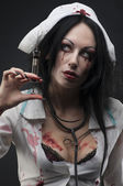 Dead nurse holding syringe with blood — Stock Photo