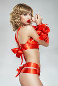 Sexy woman bound with red gift ribbon — Stock Photo