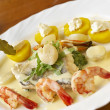 Seafood dish with spinach, potatoes and cream sauce - Stock Photo