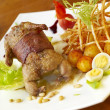 Grilled quail in bacon with fried potatoes, quail eggs and pine nuts - Stock Photo