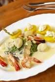 Seafood with spinach, yellow potatoes and cream sauce — Stock Photo