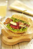 Egg burger with tomato, salad, onion and bacon — Stock Photo