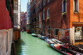 Venice canal with boats and gondolier — Stock Photo