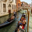 16. Jul 2012 - Gondoliers with tourists at canal in Venice, Italy — Stock Photo
