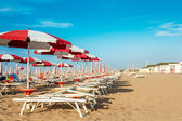 Red and white umbrellas and sunlongers on the sandy beach — Stock Photo