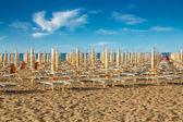 Withdrawn umbrellas and sunlongers on the sandy beach — Stock Photo
