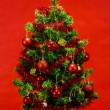 Decorated christmas tree on red background — Stock Photo #15763185