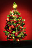 Decorated christmas tree with stars on red background — Stock Photo