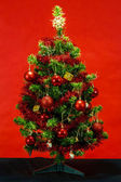 Decorated christmas tree on red background — Stock Photo