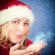 Joyful pretty woman blowing stars in red santa claus hat — Stock Photo