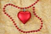 Red heart on christmas tablecloth — Stock Photo