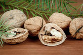 Walnuts and a cracked walnut on wooden background — Stock Photo