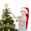 Boy with santa hat decorates the Christmas tree — Stock Photo