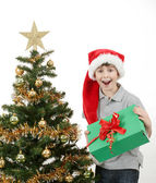 Happy boy in santa hat surprised by christmas present — Stock Photo