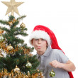 Boy with santa hat sticking out tongue at  the Christmas tree — Stock Photo