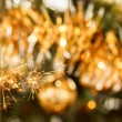 Burning sparkler and out of focus christmas tree — Stock Photo #18507911