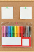 Color markers with notes on cork board — Stock Photo