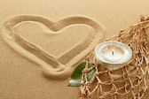 Handwritten heart on sand with lighted candles — Stock Photo
