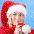 Joyful pretty woman in red santa claus hat smiling with snowflakes — Foto Stock