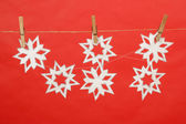 Snowflakes produced by child hanging on red background — Stock Photo