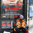 PARIS - May 7: A homeless man sitting on the street with a dog a - Stock Photo