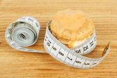 Concept of slimming, caramel cake with measuring tape — Stock Photo