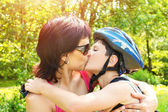 Mother kisses her son outdoor — Stock Photo