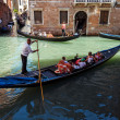 ITALY, VENICE - JULY 2012: Heavy traffic of gondolas with tourists cruising small canal on July 16, 2012 in Venice. Gondolis major mode of touristic transport in Venice, Italy. — Stock Photo #27373139