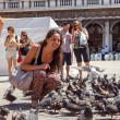 Stock Photo: ITALY, VENICE - JULY 2012: Womwith pigeons on most famous square July 16, 2012 in Venice. More th20 million tourists come to Venice annually.