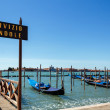 ITALY, VENICE - JULY 2012: Gondolas moor on July 16, 2012 in Venice. Gondolas are traditional flat-bottomed rowing boats that today mainly carry tourists. — Stock Photo