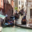 ITALY, VENICE - JULY 2012: Heavy traffic of gondolas with tourists cruising small canal on July 16, 2012 in Venice. Gondolis major mode of touristic transport in Venice, Italy. — Stock Photo #27375849