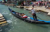 ITALY, VENICE - JULY 2012: Gondolas with tourists cruising a small Venetian canal on July 16, 2012 in Venice. Gondola is a major mode of touristic transport in Venice, Italy. — Stock Photo