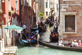 ITALY, VENICE - JULY 2012: Heavy traffic of gondolas with tourists cruising a small canal on July 16, 2012 in Venice. Gondola is a major mode of touristic transport in Venice, Italy. — Stock Photo