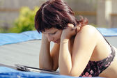 Busty woman with swimsuit reading news on tablet — Stockfoto