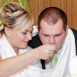 Bride feeding her groom with spoon on wedding lunch — Stock Photo #36619557