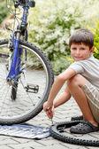 Teenager opravit kolo, měnící se zlomenou pneumatik — Stock fotografie