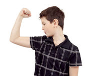 Portrait of a young boy with hand raised up and showing muscles — Stock Photo