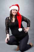 Beautiful pregnant santa woman tenderly holding her tummy — Stock Photo