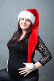 Beautiful pregnant santa woman tenderly holding her tummy — Stock fotografie