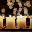 Stock Photo: Burning candle with christmas tree bokeh