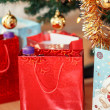 Detail of gifts under decorated christmas tree — Stock Photo